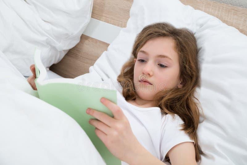 女孩阅读书在卧室 库存照片