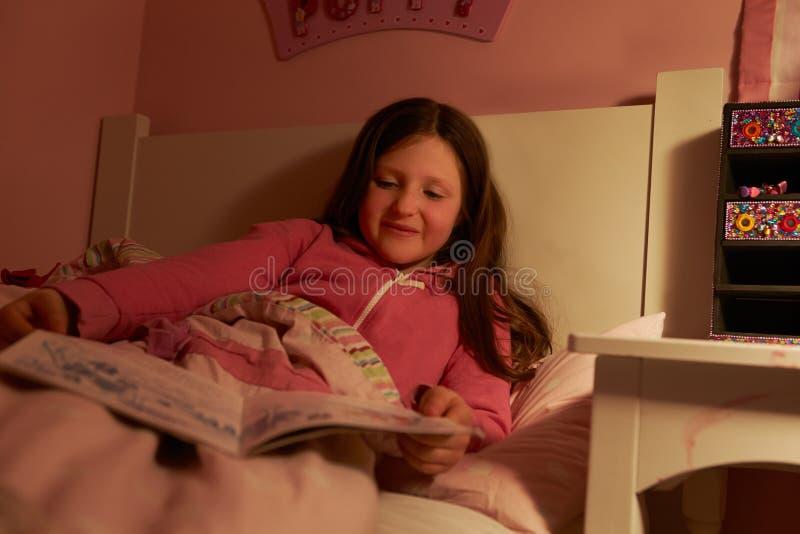 女孩阅读书在床上在晚上 库存图片