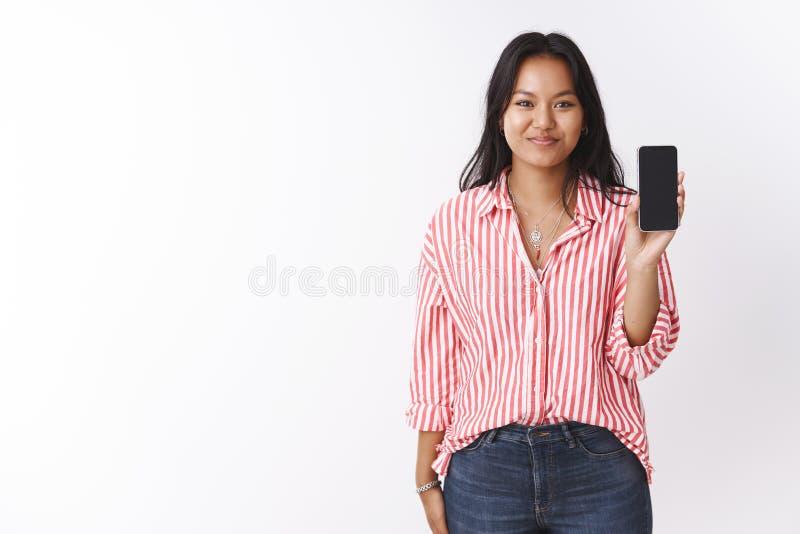 女孩陈列智能手机她建议购买 高兴愉快的可爱的年轻玻利尼西亚人女性在镶边桃红色女衬衫 库存照片