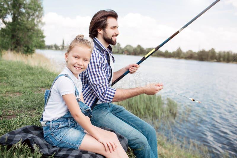 女孩除她的父亲以外坐并且看照相机 人举行gish标尺和钓鱼 集中他  库存图片