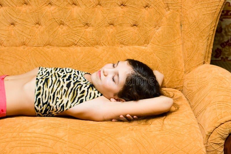 女孩青少年休眠的沙发 免版税库存照片