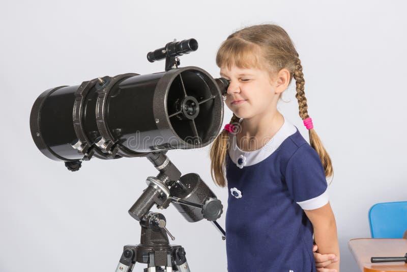女孩非职业天文学家观看的星通过望远镜 免版税库存图片
