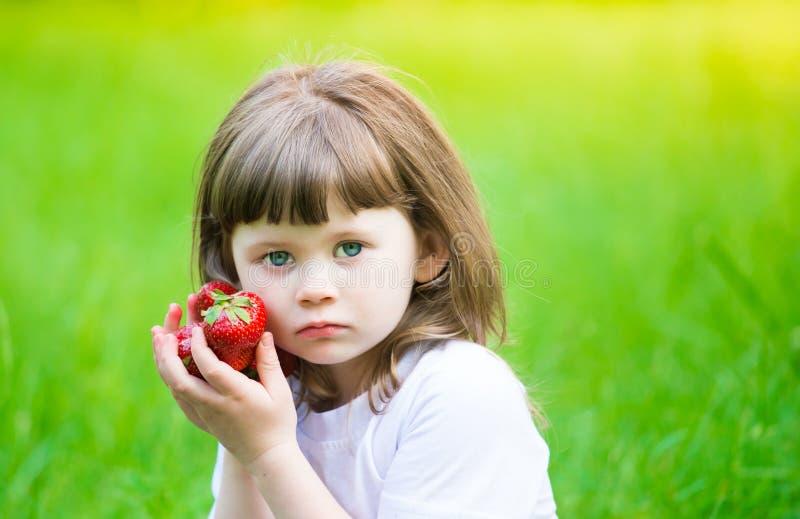 女孩面孔,草莓,哀伤的蓝眼睛,关闭  库存图片