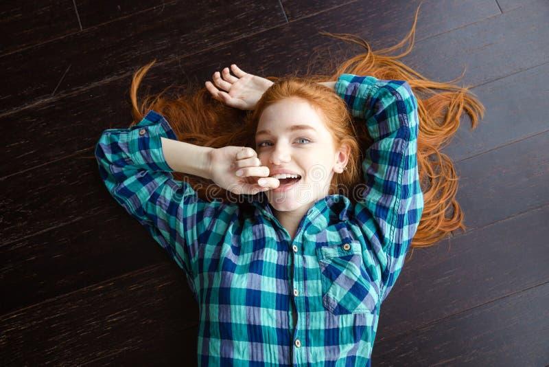 女孩顶视图说谎在地板上的格子花呢上衣的 免版税库存照片