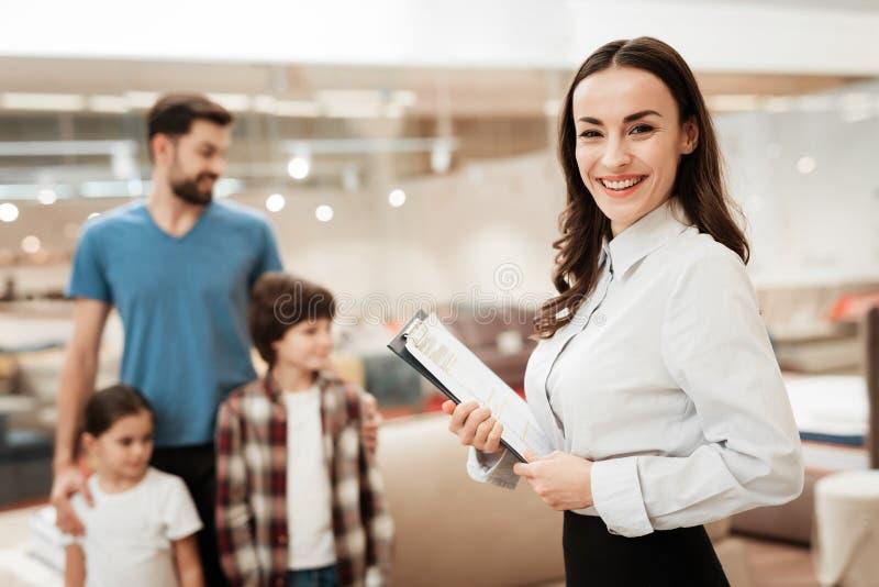 女孩顾问给有孩子的年轻父亲展示矫形床垫家具店的 免版税库存照片