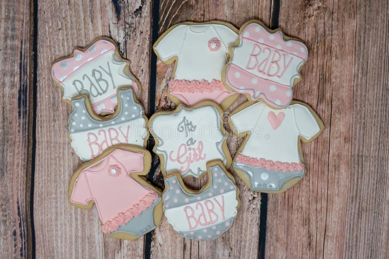 女孩题材的装饰的自创婴儿送礼会曲奇饼,装饰在桃红色,灰色的皇家在一木backg的结冰和白色 库存照片