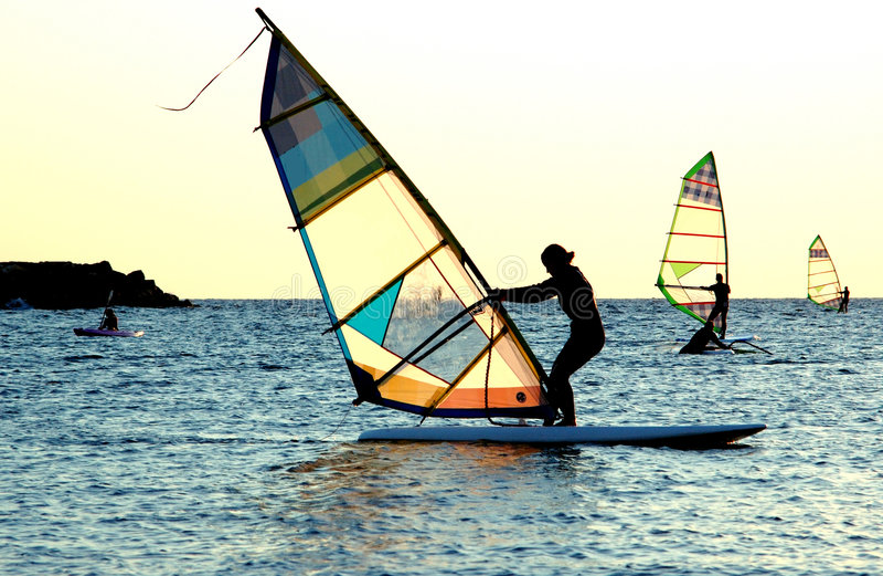 女孩风帆冲浪的年轻人 库存照片