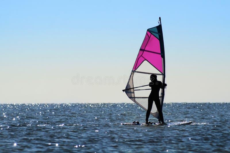 女孩风帆冲浪者的剪影 免版税库存照片
