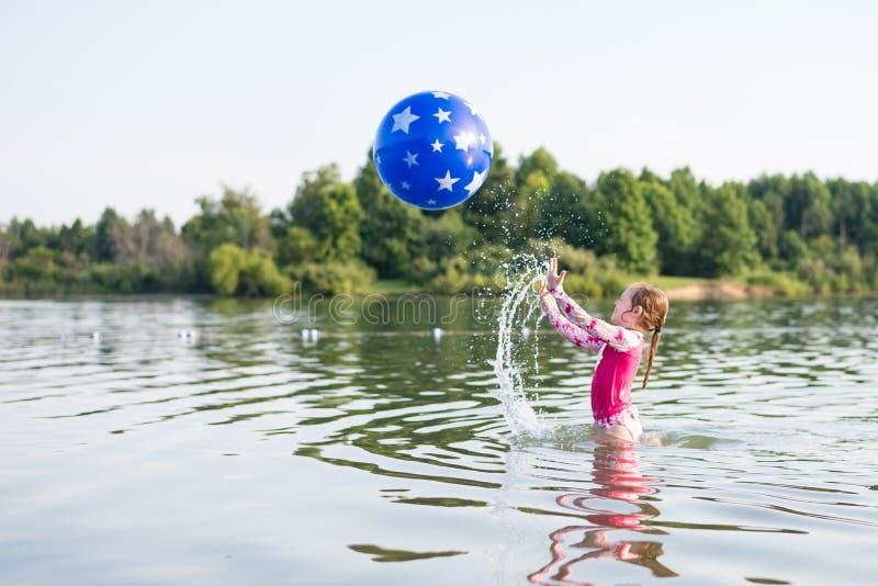 女孩飞溅的和投掷的球在湖 库存图片