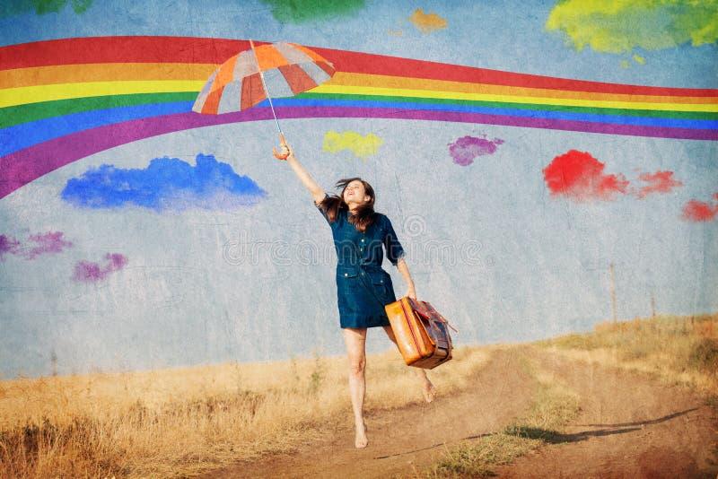 女孩飞行带着伞和手提箱 免版税库存照片