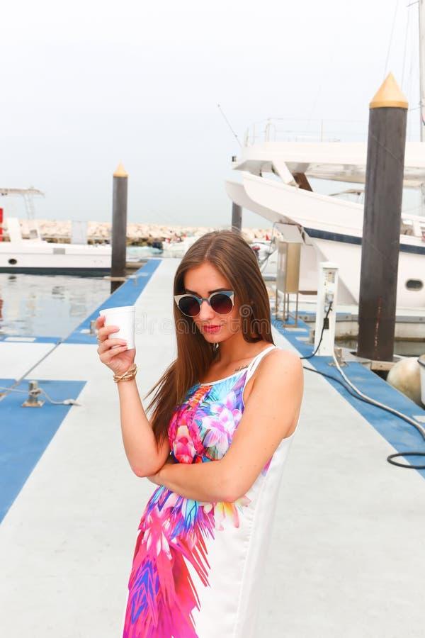 女孩饮料在小游艇船坞-迪拜的早晨coffe 库存照片