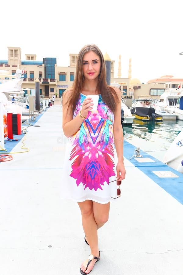 女孩饮料在小游艇船坞-迪拜的早晨coffe 免版税库存照片