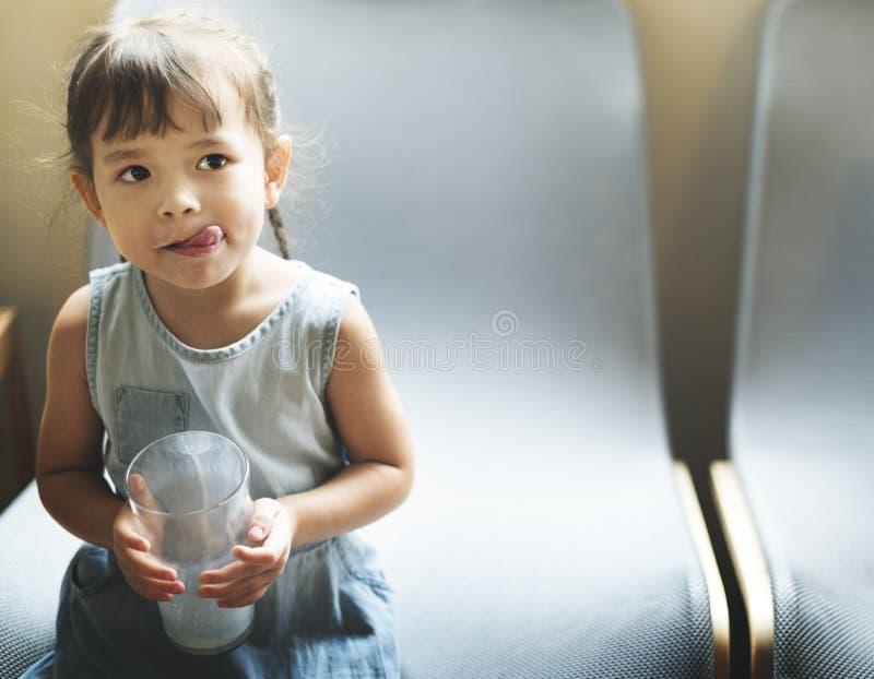 女孩饮用奶饥饿的鲜美概念 库存图片