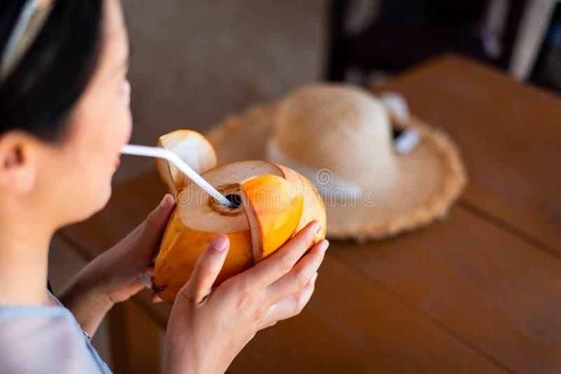 女孩饮用椰子在海滩酒吧 免版税库存图片
