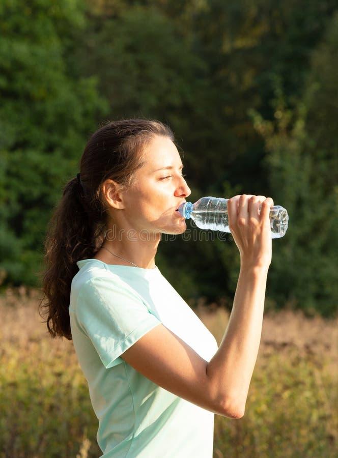 女孩饮用水户外 体育和健身 库存照片