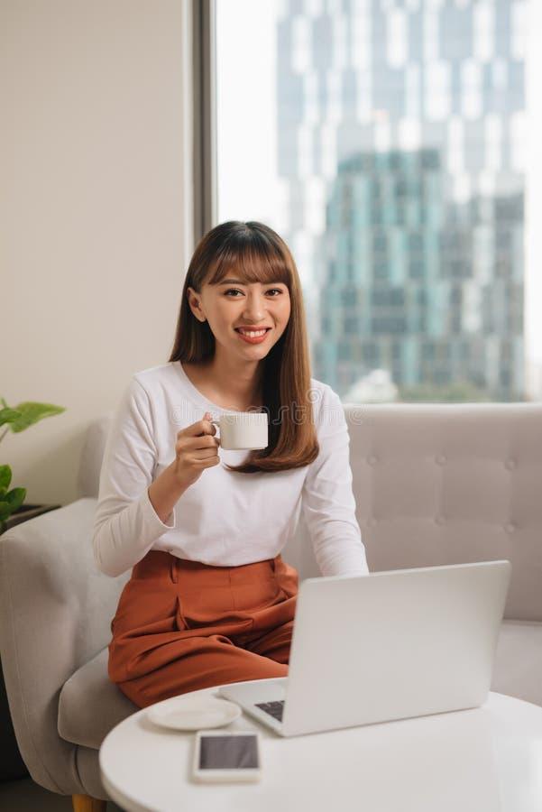 女孩饮用的早晨咖啡和使用膝上型计算机,当选址在长沙发时 库存图片