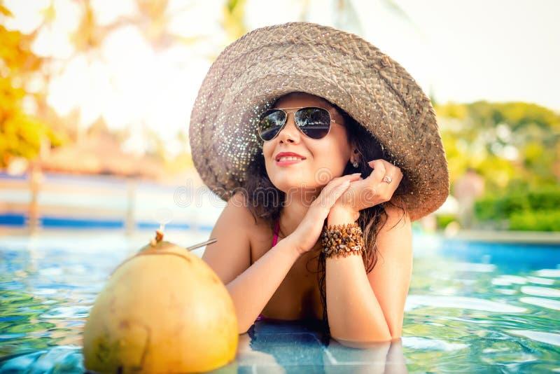 女孩饮用的椰子鸡尾酒,可爱和性感的少妇有茶点饮料在水池 库存照片
