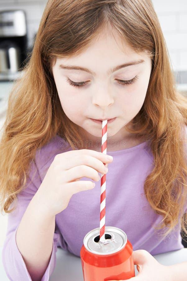 女孩饮用的罐头苏打通过秸杆 免版税库存图片