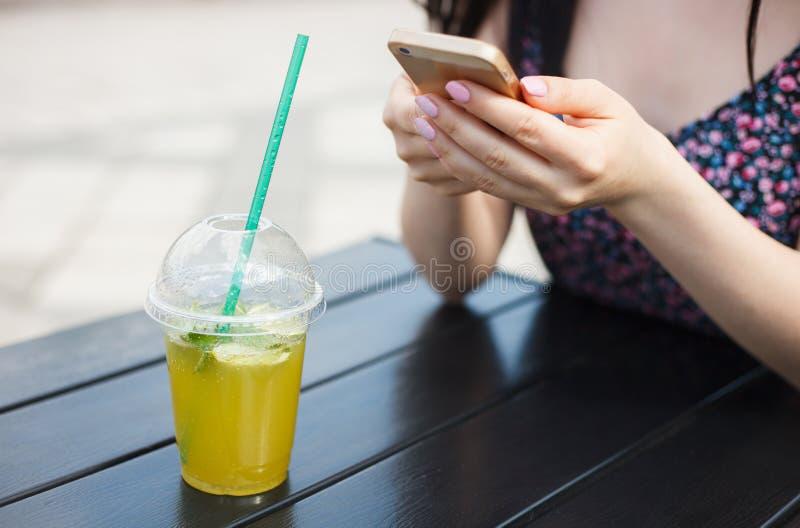 女孩饮用的mojito,当使用巧妙的电话时 免版税库存图片