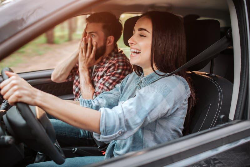 女孩驾驶汽车和笑 人除她以外坐 由于他女朋友` s驾驶,他害怕 年轻 库存图片