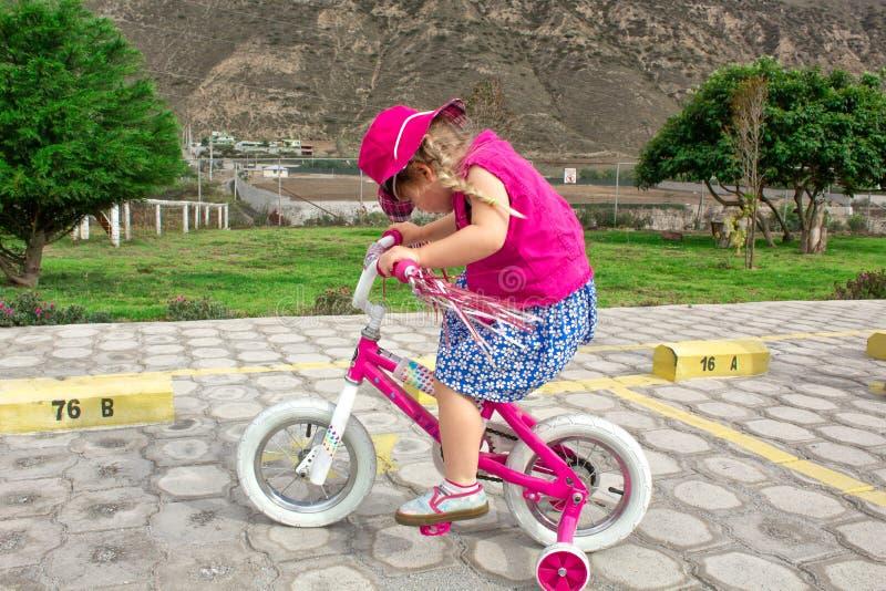 女孩骑在帽子的一辆桃红色自行车 夏天步行 在背景-山风景中  库存照片