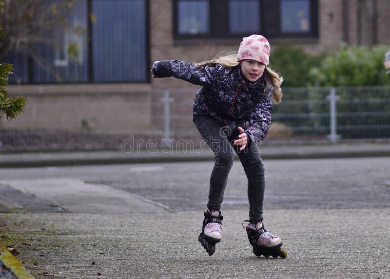 女孩骑马溜冰鞋击倒街道 库存照片