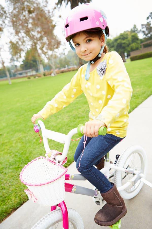 女孩骑马自行车在公园 免版税库存照片
