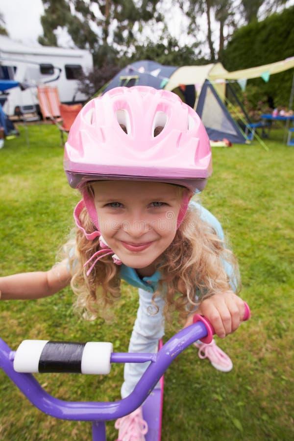 女孩骑马滑行车,家庭野营假日 库存照片