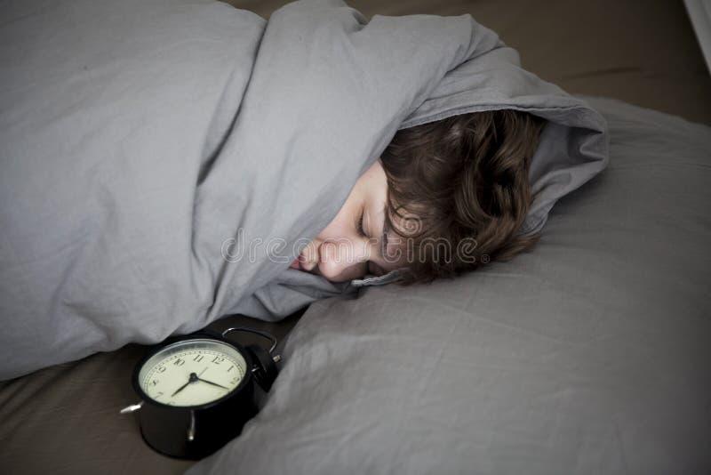 女孩,包裹在一条灰色毯子,投入她的手关闭警报 有在闹钟的六个小时 免版税图库摄影
