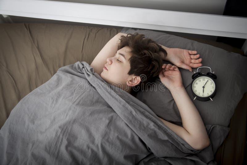 女孩,包裹在一条灰色毯子,投入她的手关闭警报 有在闹钟的六个小时 免版税库存图片