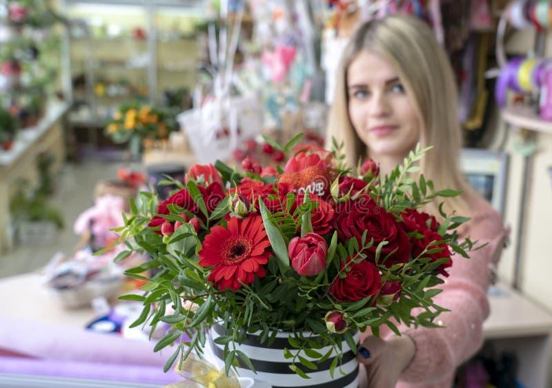女孩,卖花人设计师提供红色花美丽,欢乐花束和心脏以题字爱,特别地 免版税库存图片