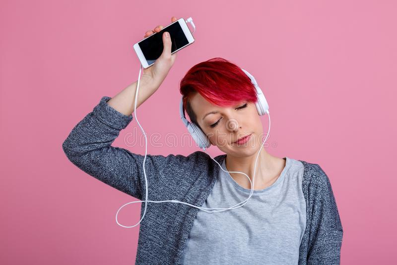 女孩,听到在耳机的音乐从电话,她的眼睛关闭了和举胳膊  在桃红色背景 库存图片