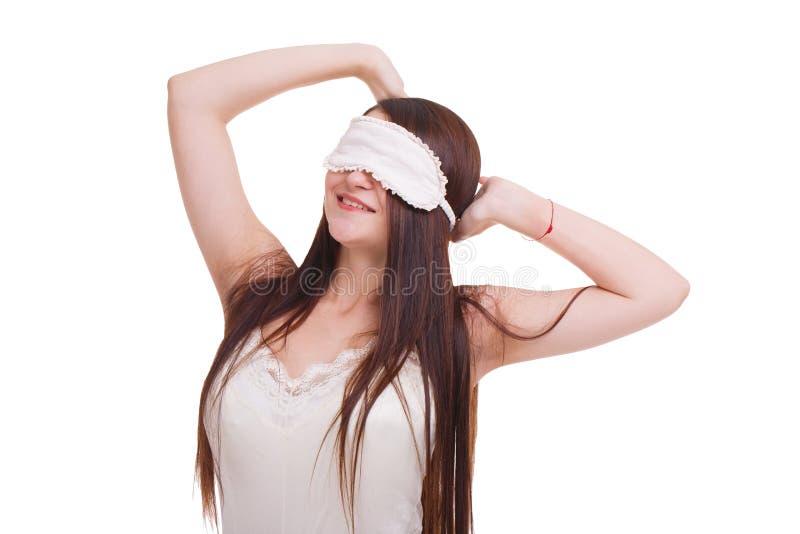女孩,戴着睡觉的一个面具,拉扯在头后的养猫的处所 背景查出的白色 免版税库存照片