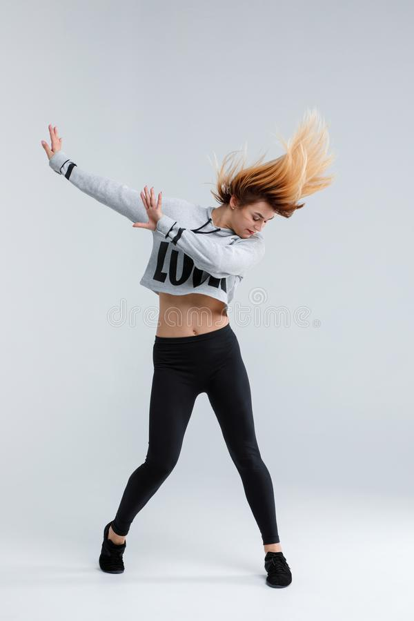 女孩,现代舞蹈家,在行动显示从舞蹈的一个元素,隔绝在白色背景 图库摄影