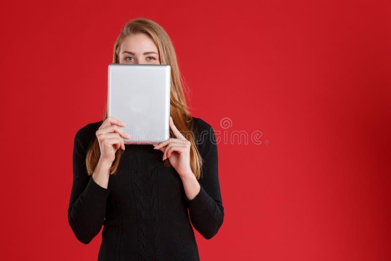 女孩,用一种灰色片剂盖她的面孔 免版税库存照片