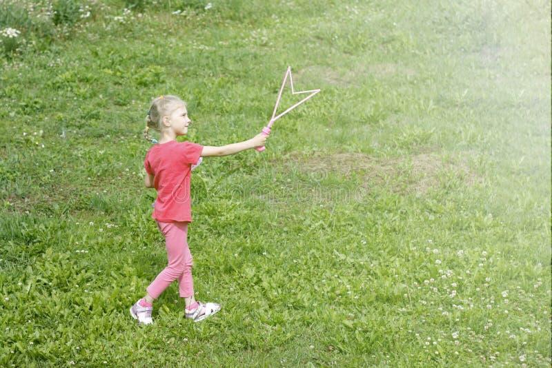 女孩,金发碧眼的女人,使用在草甸和打击泡影 库存照片