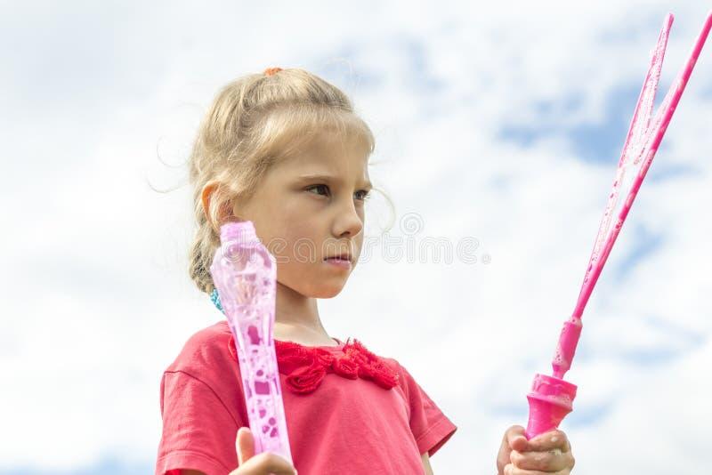 女孩,金发碧眼的女人,使用在草甸和打击泡影 免版税库存图片