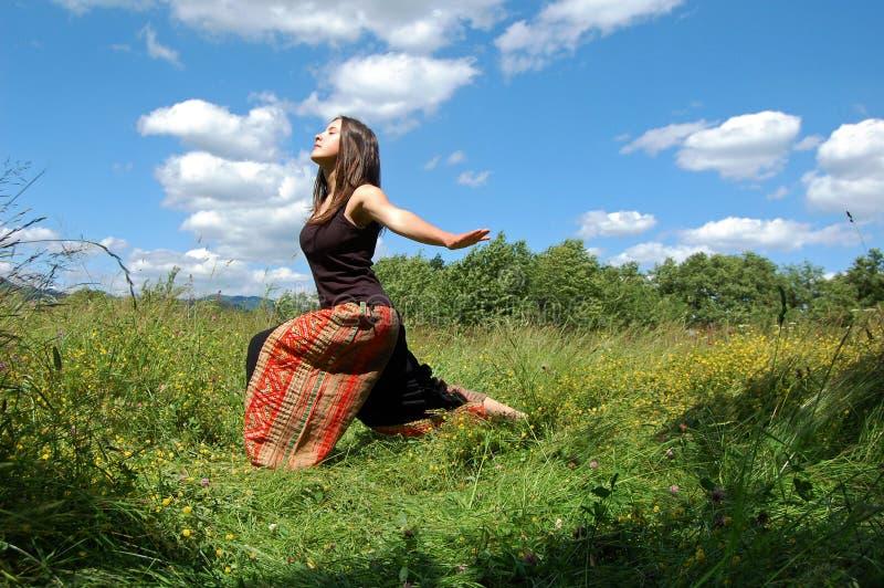女孩/做瑜伽姿势的少妇户外在自然环境里 免版税图库摄影