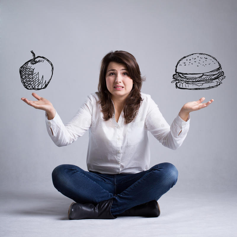女孩以关于食物的一种困境 图库摄影