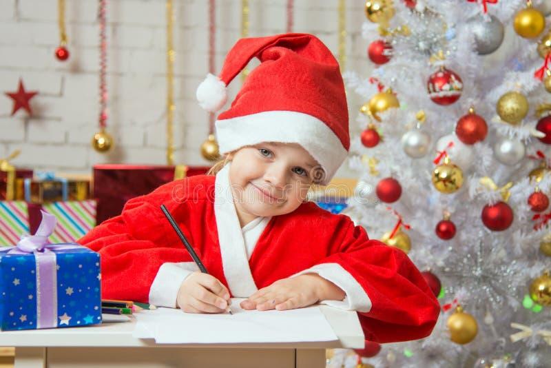 女孩给圣诞老人愿望写了 库存照片