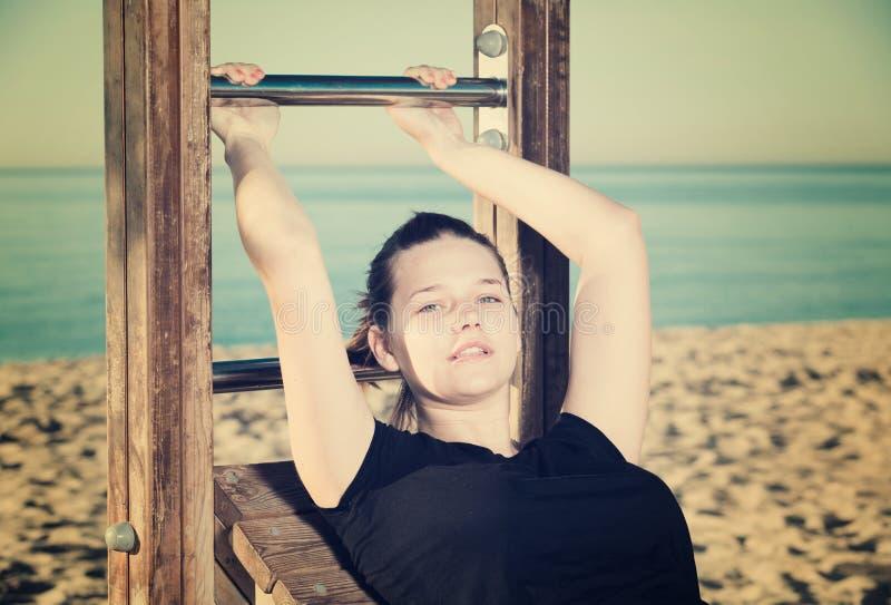 女孩20-30岁做着仰卧起坐 库存图片