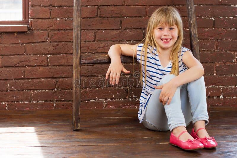 女孩6岁坐地板在砖墙旁边和填装用笑声 免版税库存图片