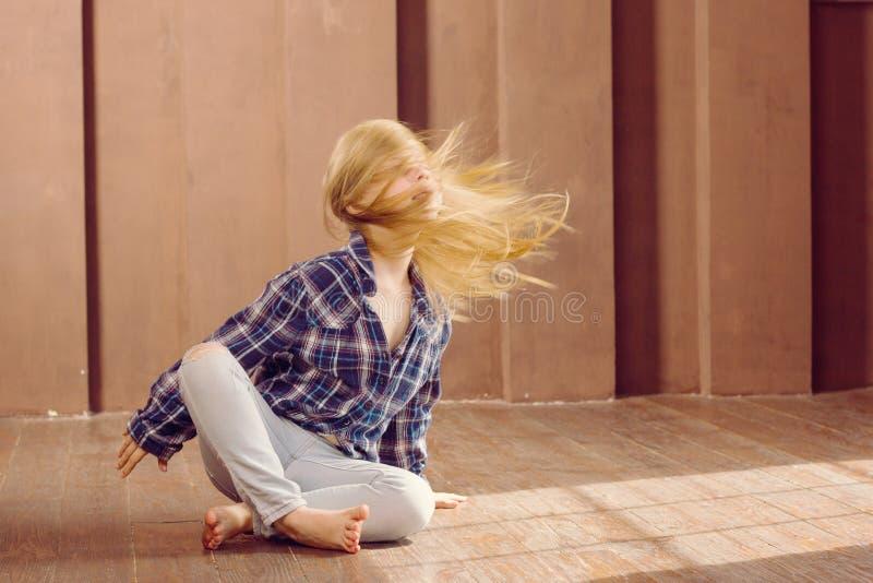 女孩6岁坐地板 头发振翼 免版税图库摄影