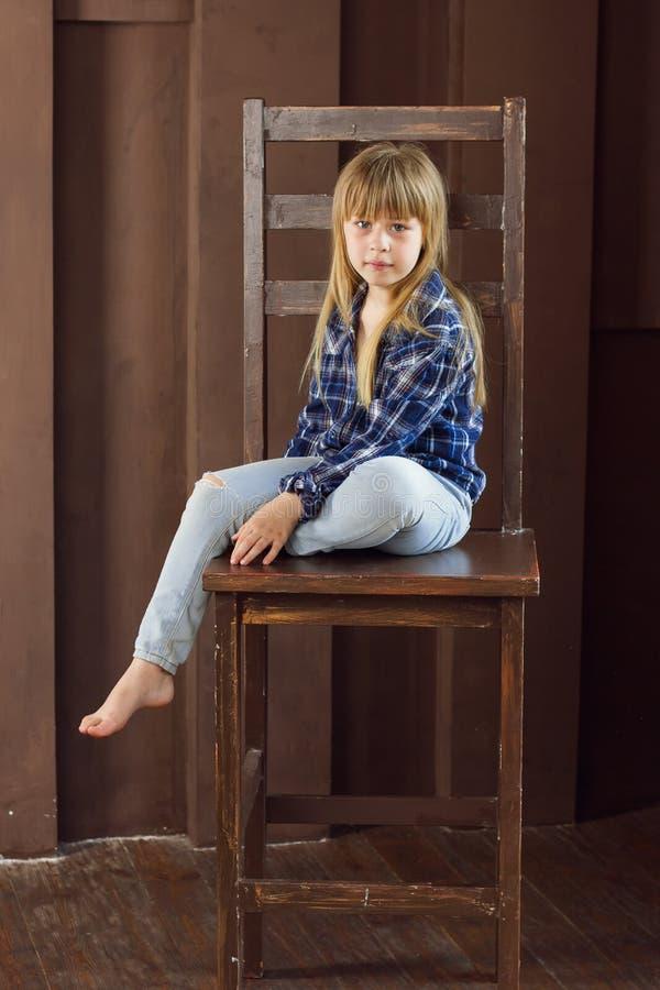 女孩6岁牛仔裤和一件蓝色衬衣坐高脚椅子在屋子里 免版税库存图片