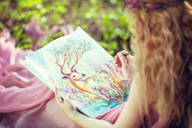 女孩绘水彩,坐在森林 免版税库存图片