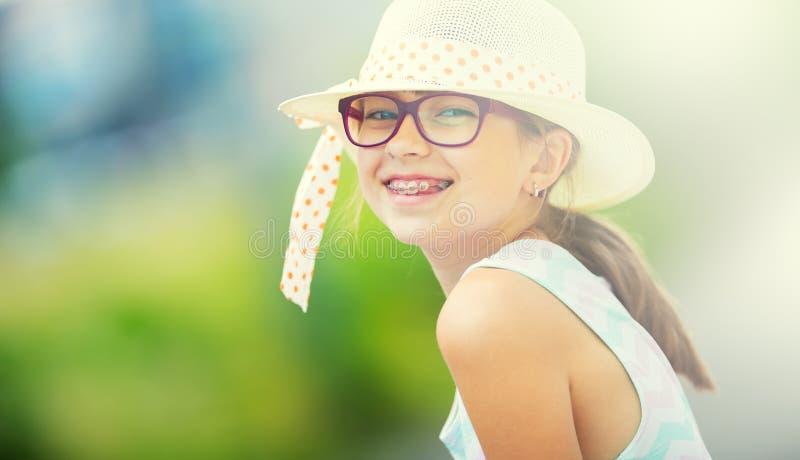 女孩 愉快的女孩青少年前青少年 戴眼镜的女孩 有牙括号的女孩 夏天成套装备的年轻逗人喜爱的白种人白肤金发的女孩 免版税图库摄影