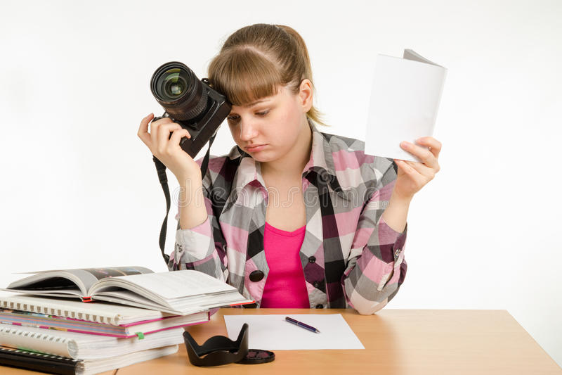 女孩读指南和讲解,设法学会如何拍照片 免版税图库摄影