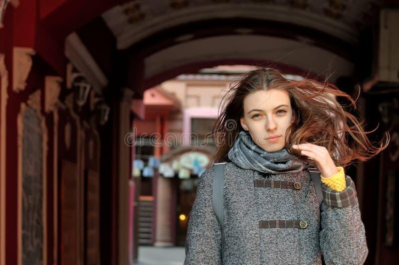 女孩从黑暗的曲拱出来,并且风吹她的头发 免版税库存照片
