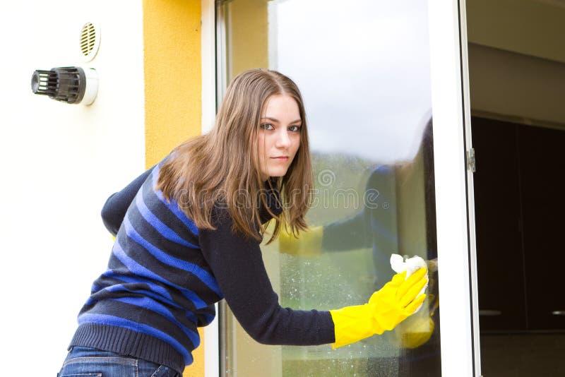 女孩洗涤的窗口 免版税库存图片