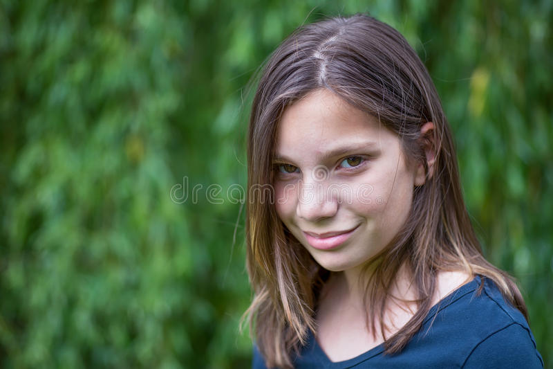女孩画象在绿色杨柳前面的 库存照片